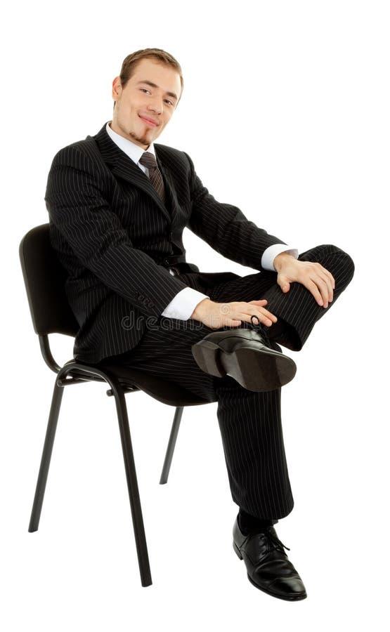Junger Mann in einem schwarzen Anzug, der auf einem ch sitzt lizenzfreie stockbilder