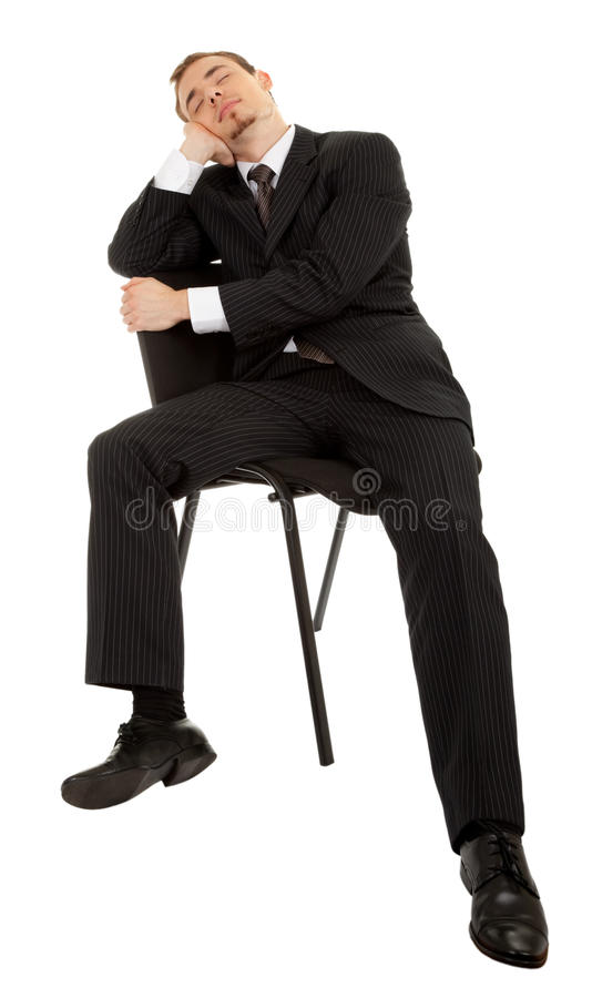 Junger Mann in einem schwarzen Anzug, der auf einem ch sitzt stockfotografie