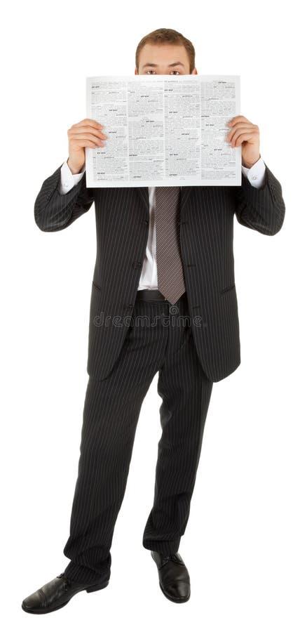 Junger Mann in einem schwarzen Anzug liest das newsp lizenzfreie stockfotografie