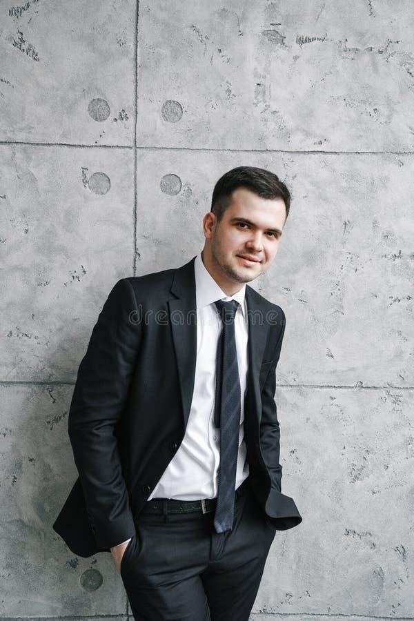 Junger Mann in einem schwarzen Anzug und in einer Bindung steht nahe einer grauen Dachboden-ähnlichen Wand und betrachtet die Kam stockfotos