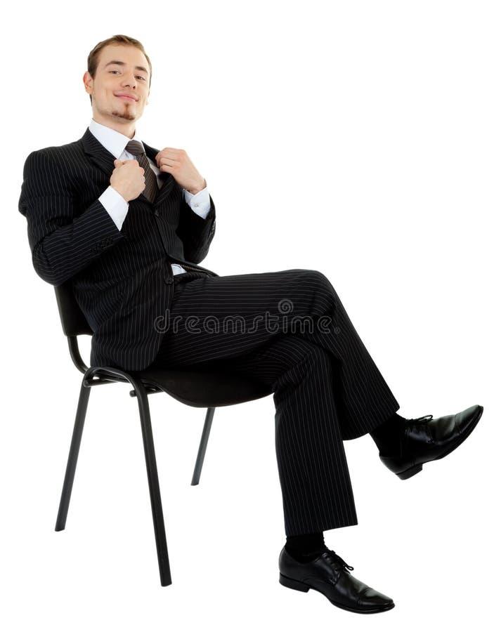 Junger Mann in einem schwarzen Anzugsitzen stockfotos