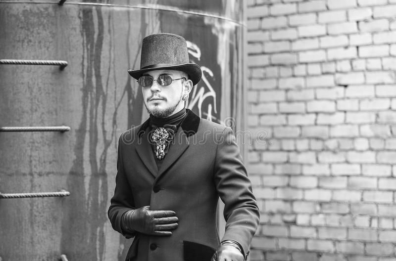 Junger Mann in einem schwarzen Mantel und in einem Zylinder in den Elendsvierteln des 19. Jahrhunderts, Dampfpunk lizenzfreie stockfotografie