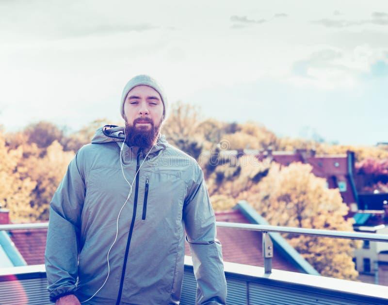 Junger Mann in einer Kappe und mit einem Bart, stehend auf der Terrasse, welche die Stadt übersieht lizenzfreie stockfotografie