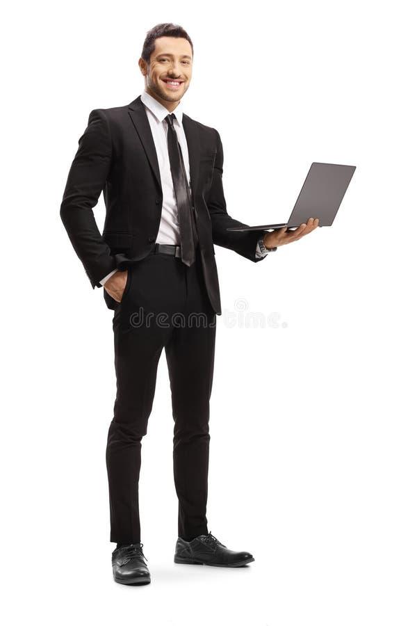 Junger Mann in einer Klage, die einen Laptop und ein Lächeln hält lizenzfreies stockbild