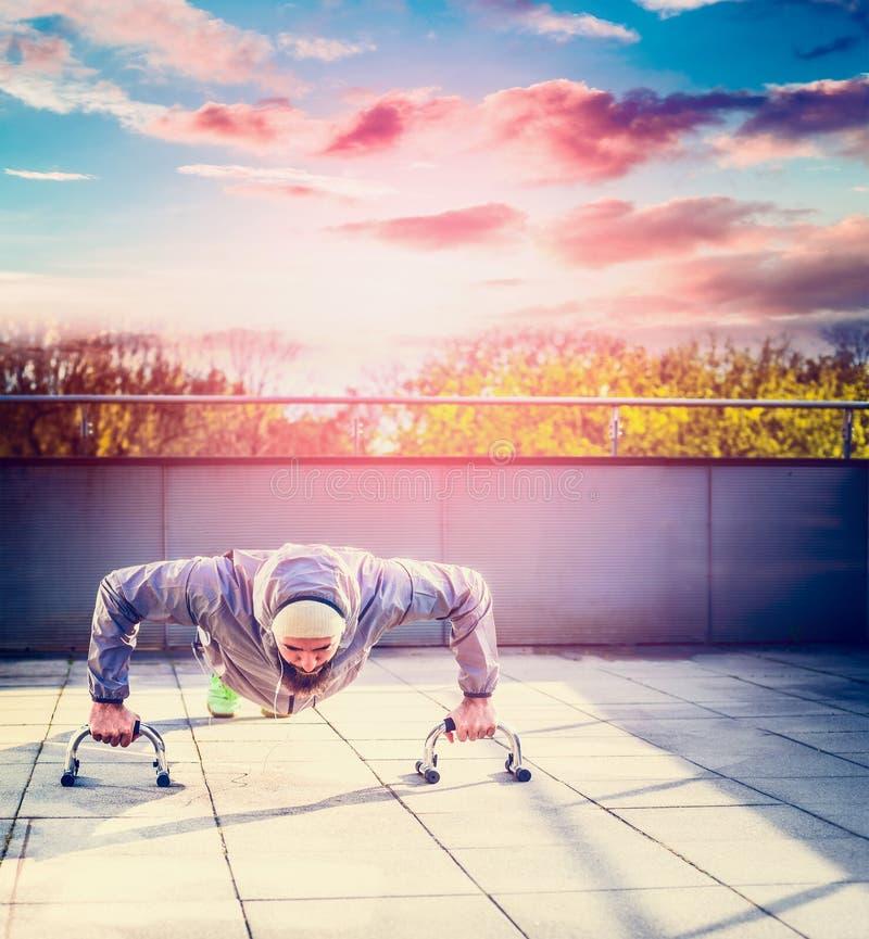 Junger Mann in einer Sportklage und -bart, die StoßUPS auf der Terrasse das Haus übersieht den Sonnenunterganghimmel und -stadt t lizenzfreies stockbild