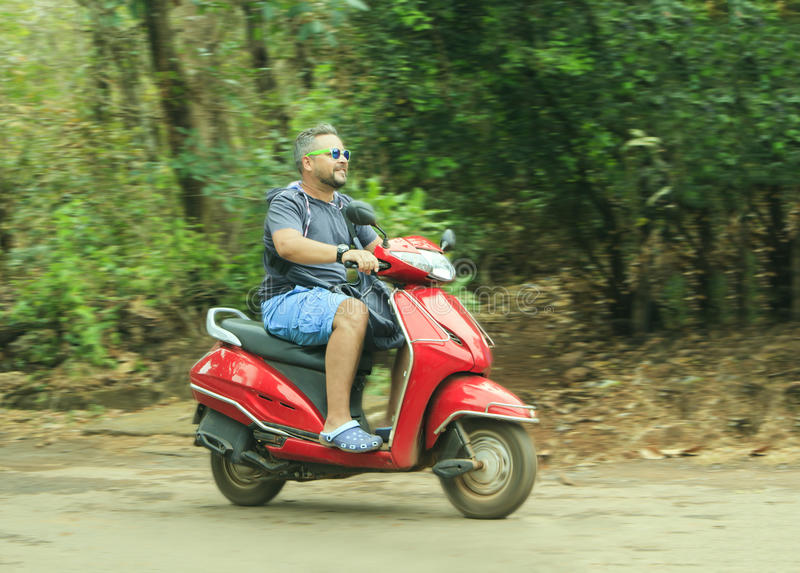 Junger Mann fährt ein rotes Motorrad lizenzfreie stockfotografie