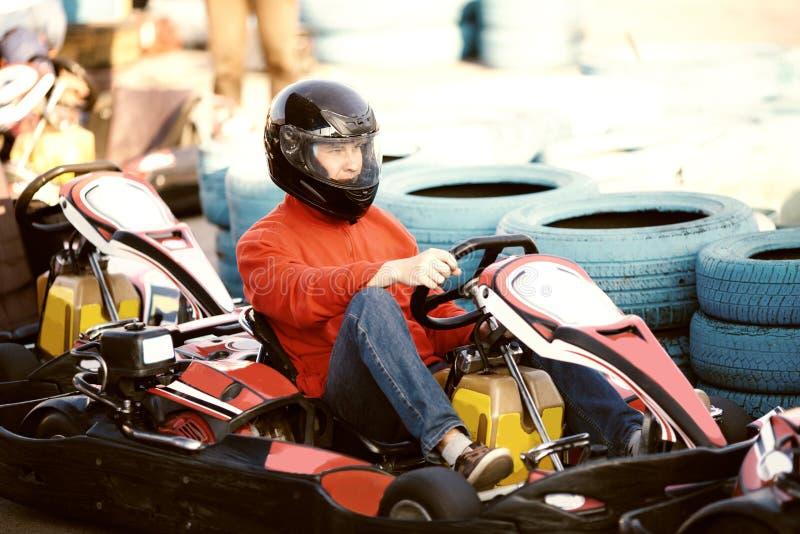 Junger Mann fährt Gokart-Auto mit Geschwindigkeit in einer Spielplatz-laufenden Bahn - Gokart ist eine populäre Freizeit-Motorspo lizenzfreie stockfotos