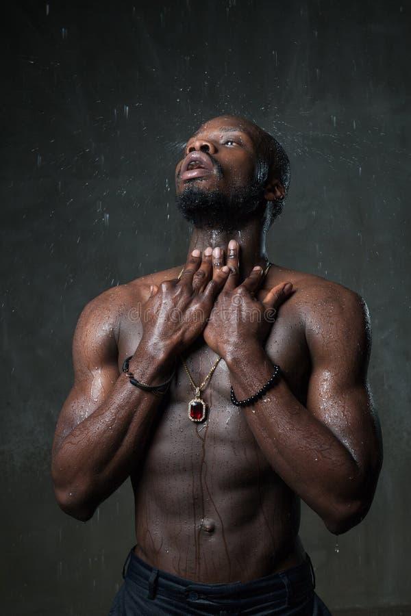 Junger Mann geeigneten starken Konstitution Afroamerikaners unter dem Regen nahe grauer konkreter Zementwand Straßenartkonzept Dr lizenzfreie stockbilder