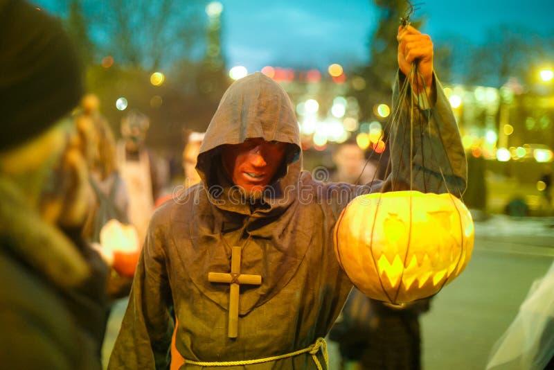Junger Mann gekleidet als Mönch, der gebogenen Kürbis zu Halloween trägt stockfoto