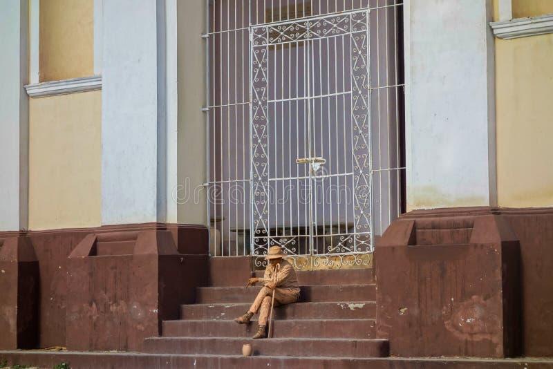 Junger Mann-gemaltes Gesicht und Körper, die mit dem Bitten der Schüssel Trinidad Cuba sitzt lizenzfreie stockfotografie