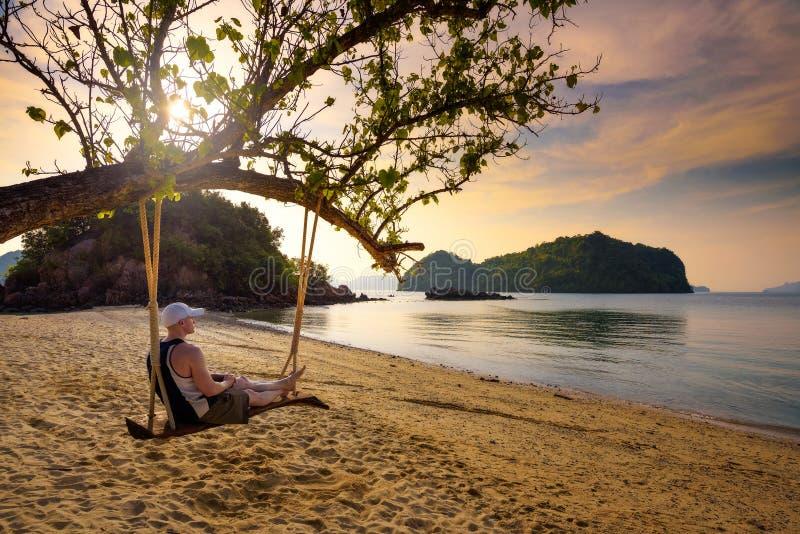 Junger Mann genießt Sonnenuntergang auf einem Schwingen an einem Strand in Thailand stockfotos