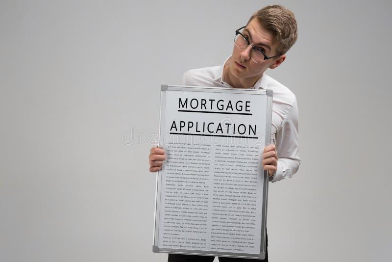 Junger Mann hält vor ihm das Plakat mit Antrag auf Hypothekendarlehen lokalisiert auf hellem Hintergrund lizenzfreie stockbilder