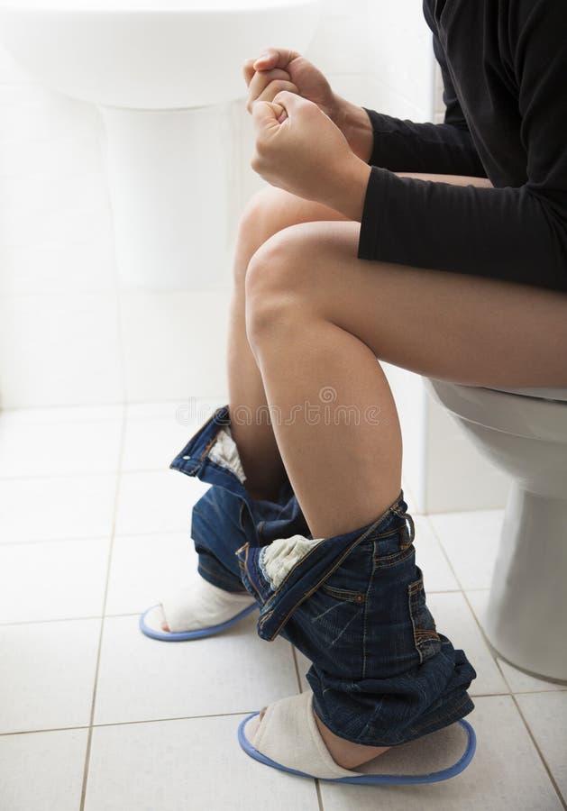 Junger Mann haben Verstopfungs- oder Diarrhöeprobleme lizenzfreie stockfotografie