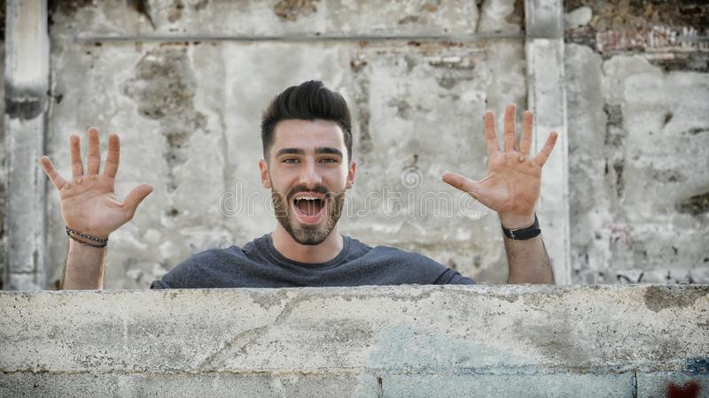 Junger Mann, heraus knallend von hinten eine kleine Wand lizenzfreie stockfotografie