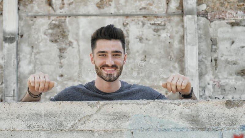 Junger Mann, heraus knallend von hinten eine kleine Wand lizenzfreies stockbild