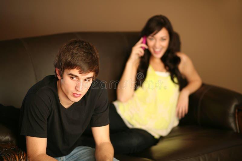 Junger Mann ignoriert von der Freundin am Telefon stockbilder