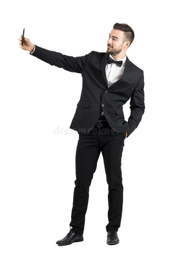 Junger Mann im Anzug mit der Fliege, die selfie mit Mobiltelefon nimmt stockbilder
