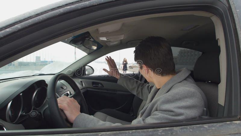 Junger Mann im Auto geht für seine Freundin stockfoto