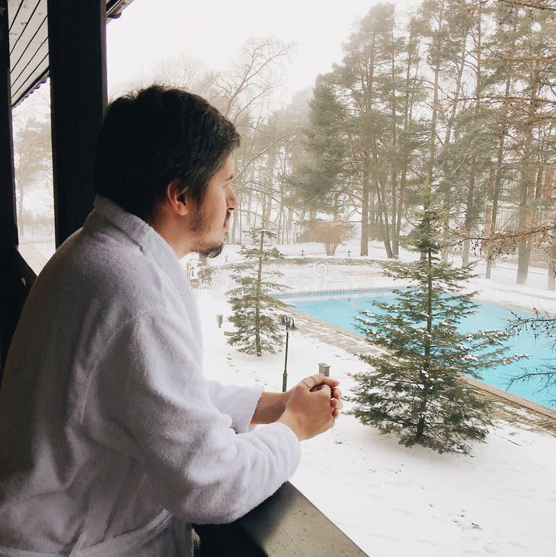 Junger Mann im Bademantel, der am Balkon im Winter bleibt und Swimmingpool betrachtet lizenzfreies stockfoto