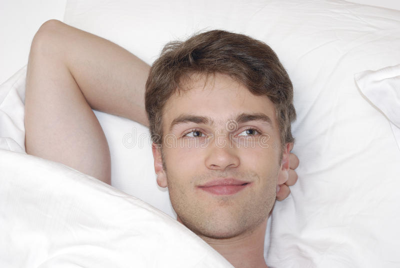 Junger Mann im Bett lizenzfreies stockbild