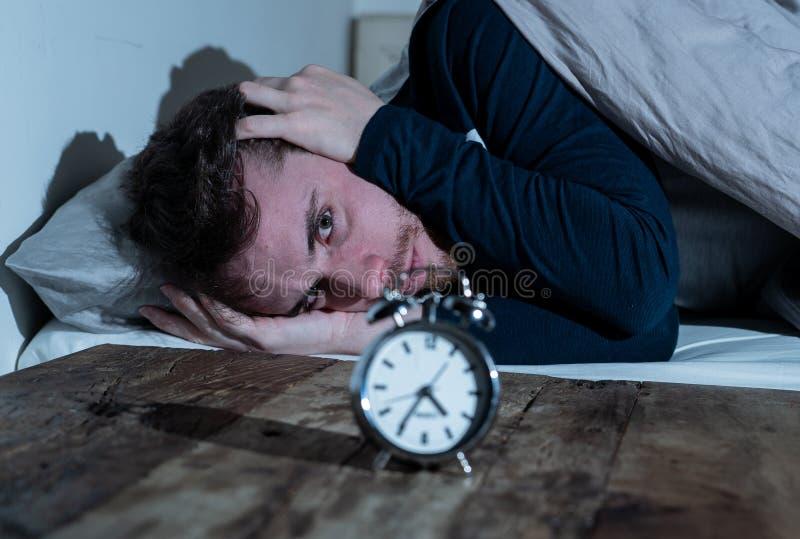 Junger Mann im Bett mit dem Weckergef?hl hoffnungslos und der Bedr?ngnis nicht f?hig, mit Schlaflosigkeit zu schlafen stockbilder