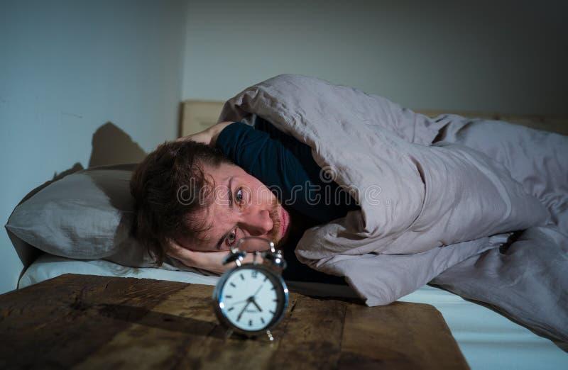 Junger Mann im Bett mit dem Weckergef?hl hoffnungslos und der Bedr?ngnis nicht f?hig, mit Schlaflosigkeit zu schlafen stockfoto