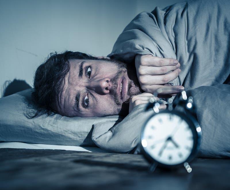 Junger Mann im Bett mit dem Weckergef?hl hoffnungslos und der Bedr?ngnis nicht f?hig, mit Schlaflosigkeit zu schlafen stockbild