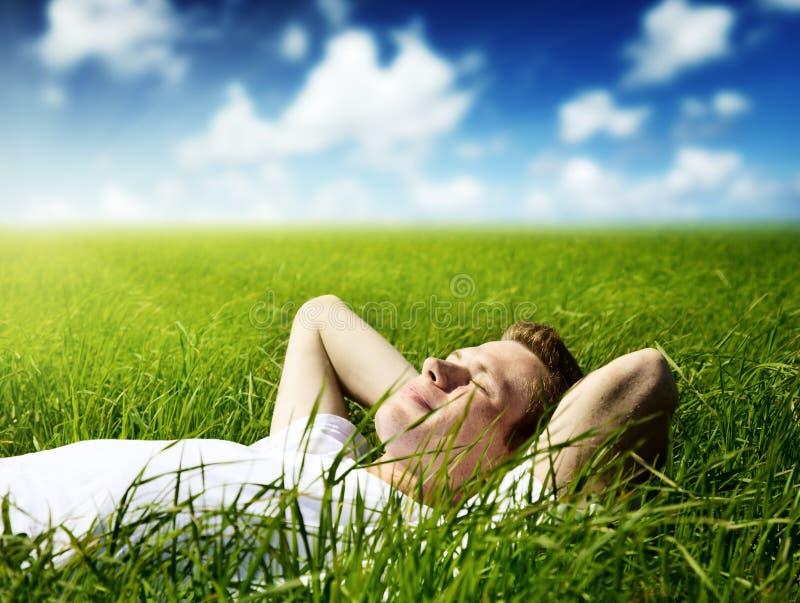 Junger Mann im Gras lizenzfreie stockbilder