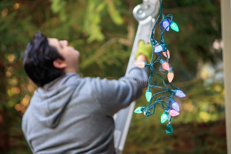 Junger Mann im Grau, das eine Leiter klettert, um für Weihnachten zu verzieren lizenzfreies stockbild