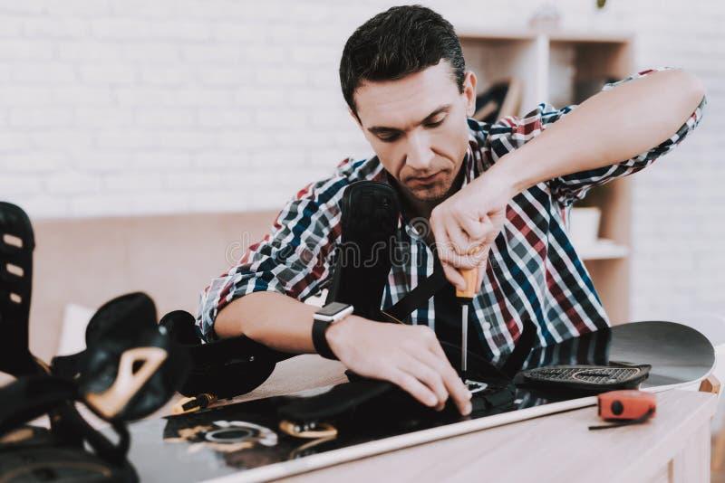 Junger Mann im Hemd, das zu Hause Snowboard repariert stockfoto
