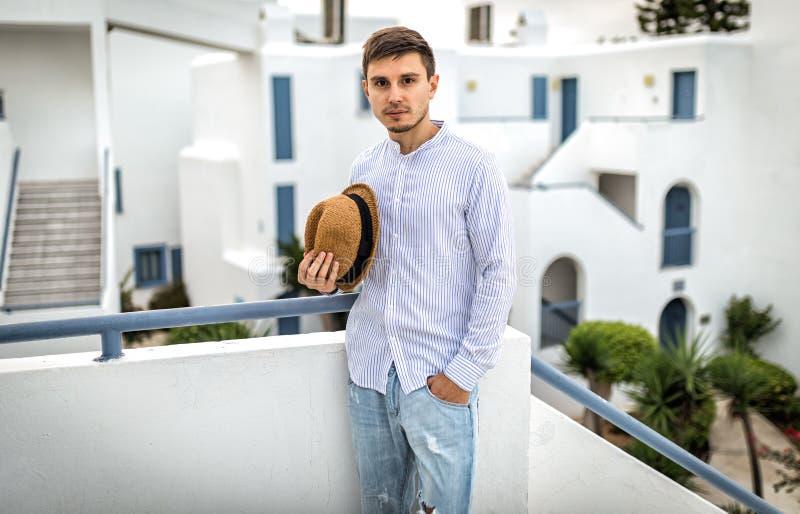 Junger Mann im Hemd des europäischen Auftritthutes Schöner Sommerhintergrund in Italien oder in Griechenland Santorini lizenzfreies stockbild