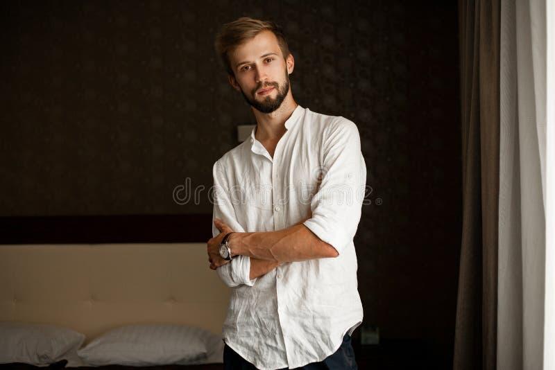 Junger Mann im Hemd steht nahes Fenster stockfoto