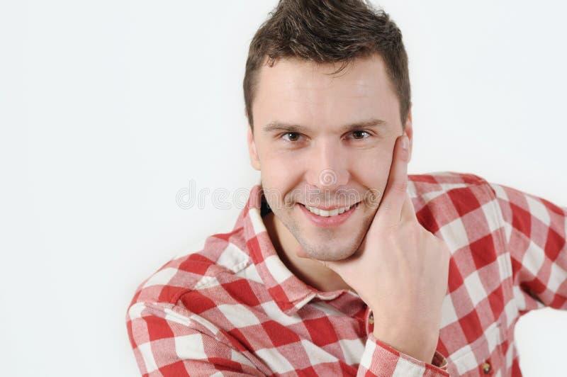 Junger Mann im Hippie-Hemd, das Hand auf Kinn und Stellung gegen weißen Hintergrund hält stockfoto