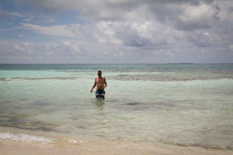 Junger Mann im Meer stockbild