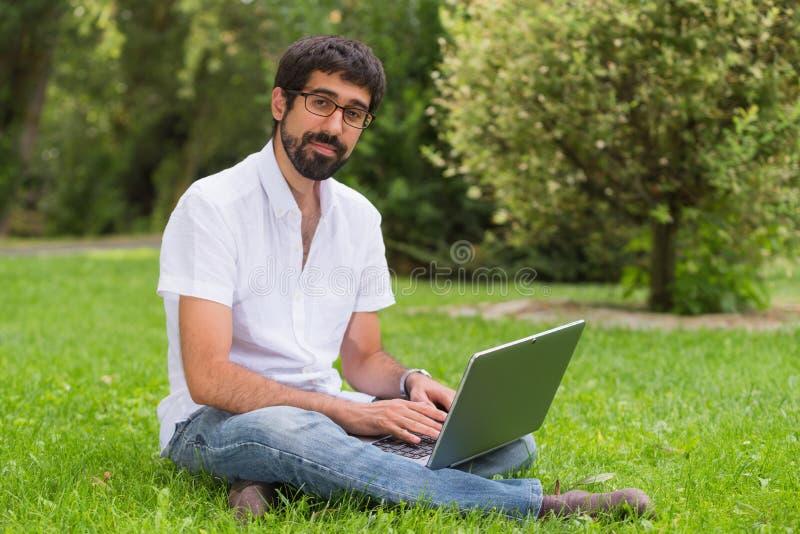 Junger Mann im Park, der auf dem Gras mit einem Laptop sitzt lizenzfreie stockfotografie