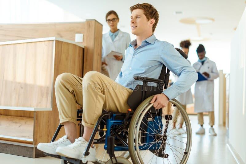 Junger Mann im Rollstuhl, der unten einen Krankenhauskorridor mit Doktoren rollt lizenzfreie stockbilder