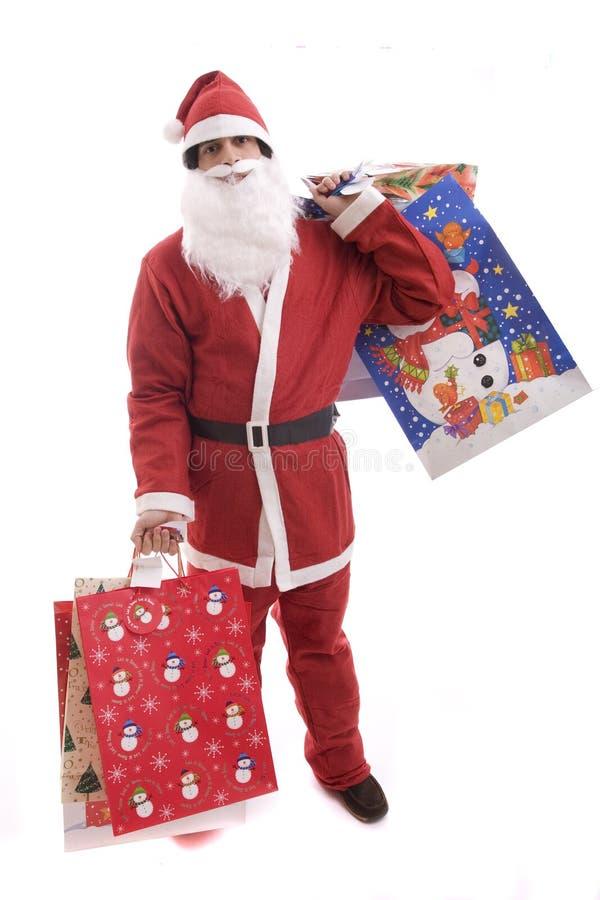 Junger Mann im Sankt-Kostüm, voll von den Geschenken stockbilder