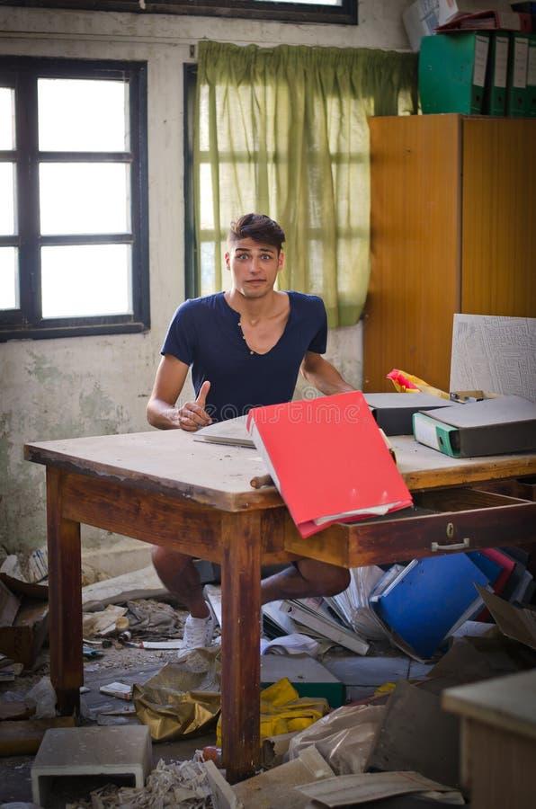 Junger Mann im sehr unordentlichen Büro, das verwirrt schaut lizenzfreies stockfoto