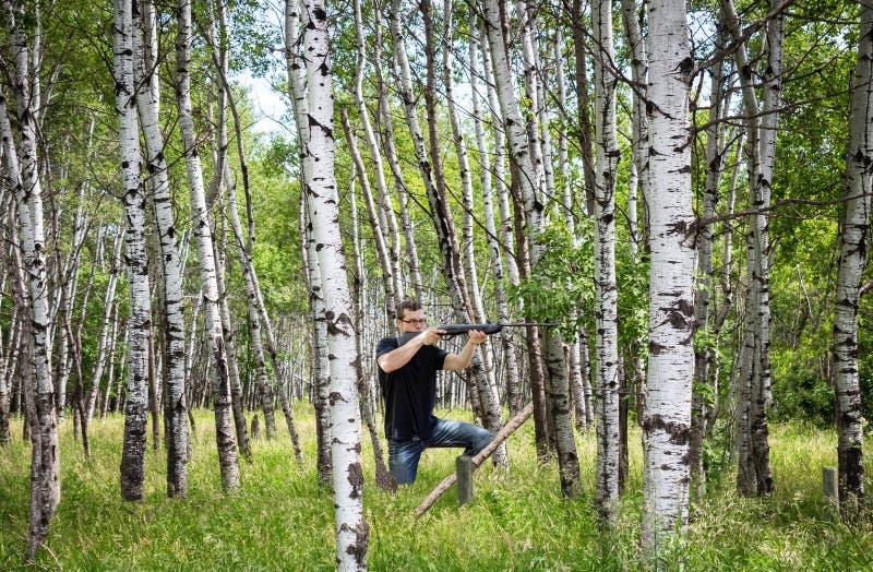 Junger Mann im Wald, der sein Gewehr in der Sommerzeit schießt stockbild