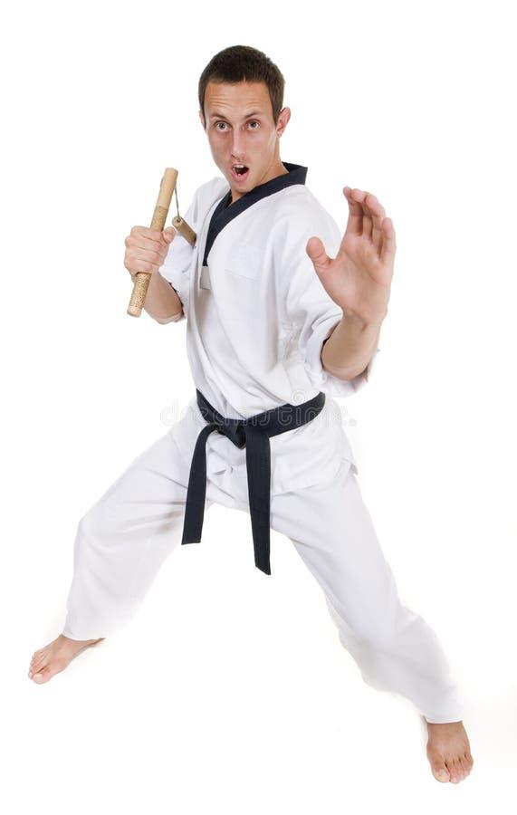 Junger Mann im weißen Kimono mit nunchaku lizenzfreie stockbilder