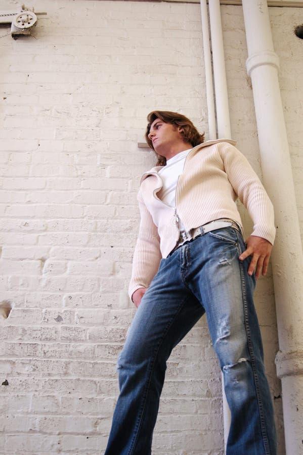 Junger Mann innen auf weißem Ziegelstein lizenzfreie stockbilder