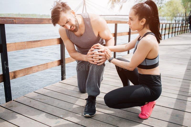 Junger Mann ist auf der Brücke mit seiner Freundin Er hat Schmerz in seinem Knie Mädchen versucht, ihm zu helfen, indem sie sie h stockbilder