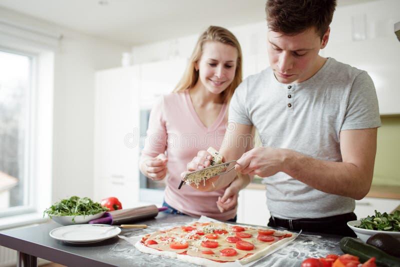 Junger Mann ist Reibkäse auf der Pizza lizenzfreies stockfoto