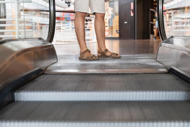 Junger Mann kurz gesagt steigt auf eine Rolltreppe stockfotografie