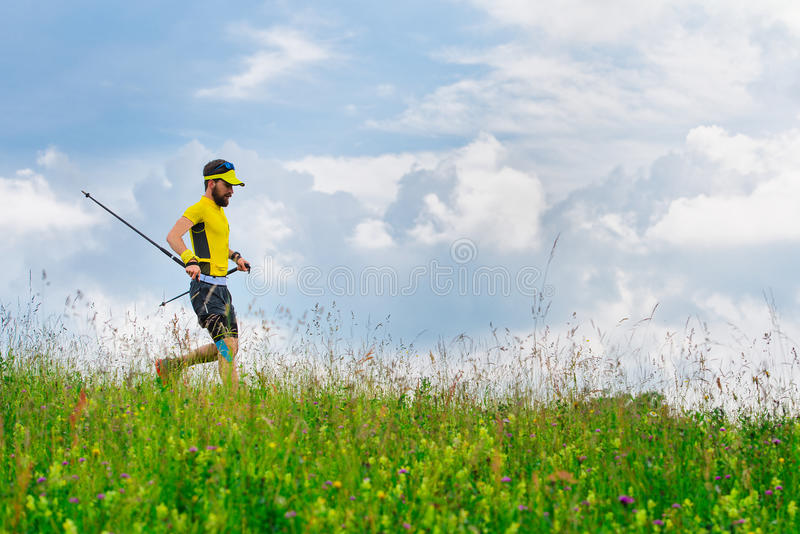Junger Mann läuft unten in das grüne Gras beim Üben von Nordic w stockfotografie
