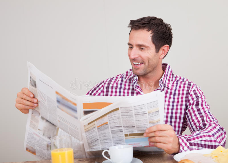 Junger Mann-Lesezeitung am Frühstück lizenzfreie stockbilder