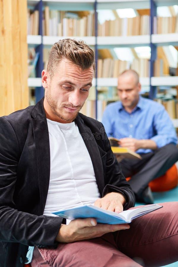 Alter Mann Liest Buch Zu Seinem Partner Vor Stockfoto