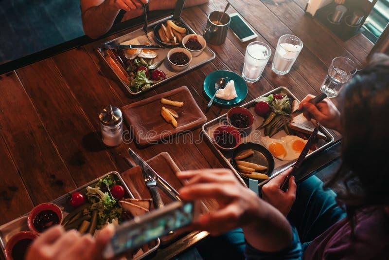Junger Mann macht ein Foto seines Lebensmittels für Soziales Netz beim Frühstücken im Café Internet-Suchtkonzept lizenzfreies stockbild
