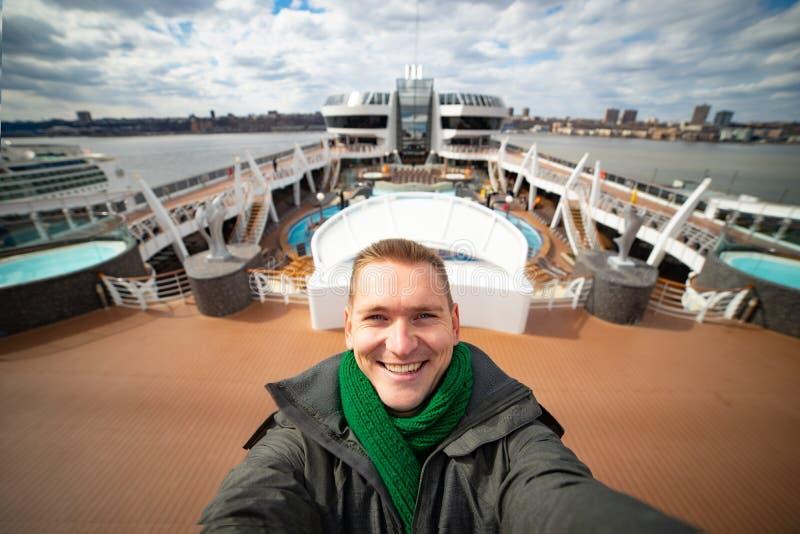 Junger Mann macht selfie mit enormem Kreuzschiff und Stadt auf Hintergrund Konzept von glücklichen Ferien und von Reisen stockfotografie