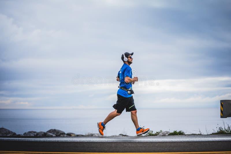 Junger Mann Marathoner an ungefähr 7km des Abstandes allein auf der Seite lizenzfreie stockfotografie